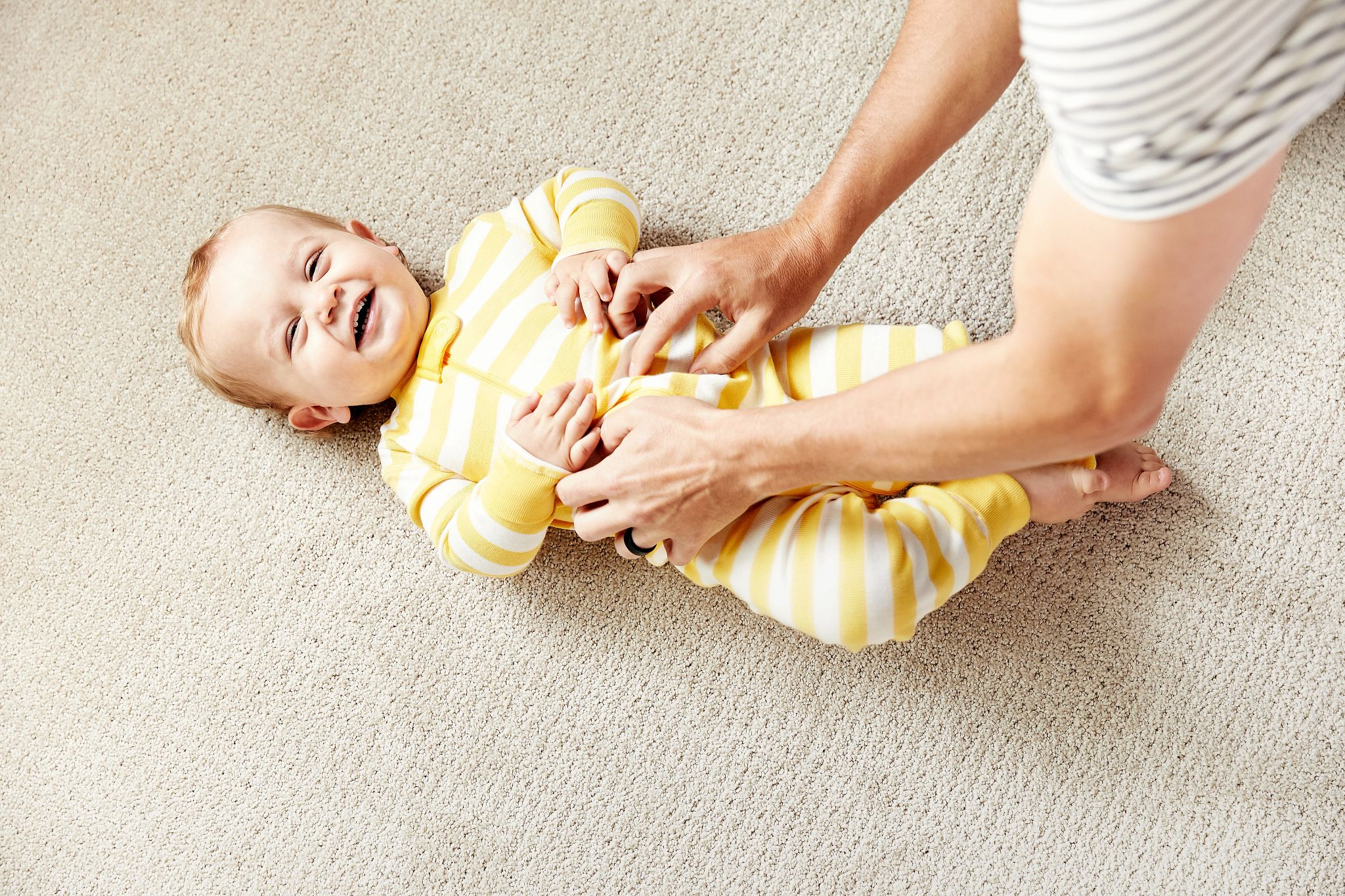Image of happy baby lounging on carpet style Translate in color Biscuit.tif